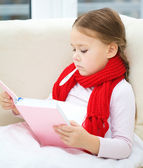 Ill little girl with thermometer is reading book — Stock Photo