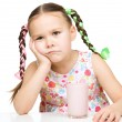 Gloomy little girl doesn't want to drink milk — Stock Photo