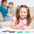 Little girl is playing with plasticine - Stock Photo