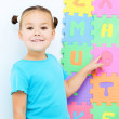 Little girl is pointing at letter O on alphabet — Stock Photo