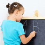 bambina sta scrivendo su una lavagna — Foto Stock