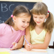 Little girls are writing using a pen — Stock Photo #18869883