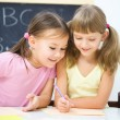 Stock Photo: Little girls are writing using a pen