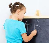 Little girl is writing on a blackboard — Stock Photo
