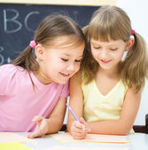 Little girls are writing using a pen — Fotografia Stock