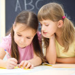 Little girls are writing using a pen — Stock Photo #18944963
