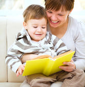 Mother is reading book for her son — Stockfoto