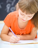 Little girl is writing using a pen — Stockfoto