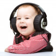 Cute little boy enjoying music using headphones - Stock Photo