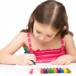 Little girl is drawing using a crayon - Stock Photo