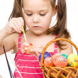 Little girl is painting eggs preparing for Easter - Stock Photo