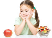 Little girl choosing between apples and sweets — Foto de Stock