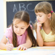 Little girls are writing using a pen — Stock Photo #19539855