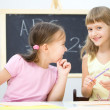 Little girls are writing using a pen - Stock Photo