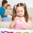 Little girl is playing with plasticine — Stock Photo #20404523