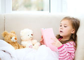 Little girl is reading a story for her teddy bears — Stockfoto