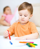 Little boy is drawing on white paper — Photo