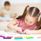 Little girl is playing with plasticine — Stock Photo