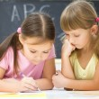 Little girls are writing using a pen — Stock Photo #21741963
