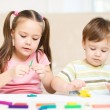 Sister and brother are playing with plasticine - Stock Photo