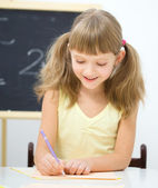 Little girl is writing using a pen — Stock Photo