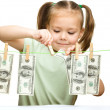 Cute little girl is playing with paper money — Stock Photo #21961199