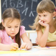 Little girls are writing using a pen — Stock Photo #21961947