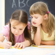 Little girls are writing using a pen — Stock Photo #21962101