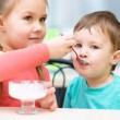 Girl is feeding his little brother with ice-cream — Stock Photo