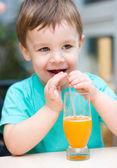 Kleiner junge mit glas orangensaft — Stockfoto