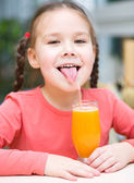 Little girl is drinking orange juice — Stock Photo