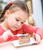 Petite fille mange gâteau dans salon — Photo