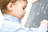 Little boy is writing on blackboard — Stock Photo