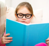 Little girl is reading a book — Stock Photo