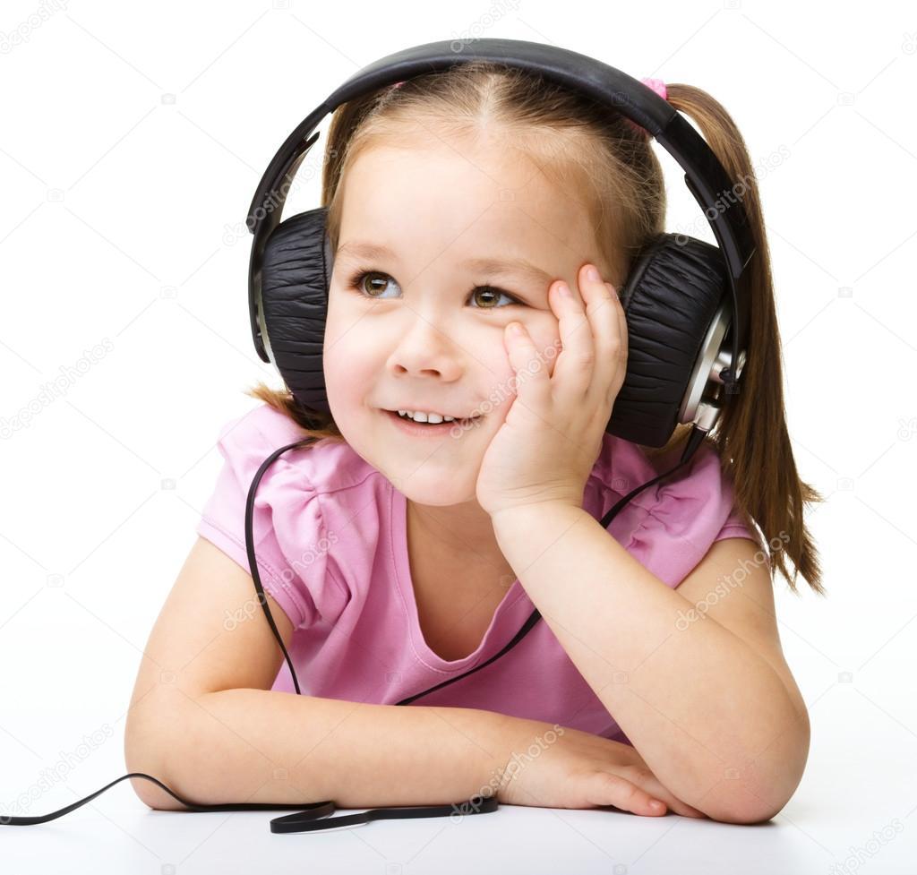 可爱的小女孩享受音乐使用头戴式耳机