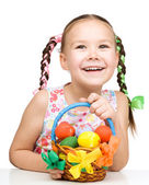 Kleines mädchen mit korb voller bunter eier — Stockfoto