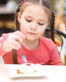 Menina está comendo bolo no salão — Foto Stock