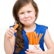Cute little girl is eating carrot — Stock Photo #22943782