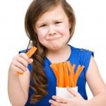 Cute little girl is eating carrot — Stock Photo #22943782