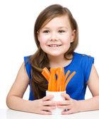 Cute little girl is eating carrot — Stock Photo