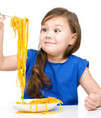 Little girl is eating spaghetti — Photo