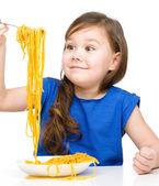Niña está comiendo espaguetis — Foto de Stock