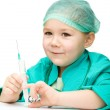 Cute little girl is playing doctor with syringe — Stock Photo