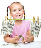 Cute little girl is playing with paper money — Stock Photo