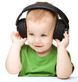 Cute little boy enjoying music using headphones — Stock Photo