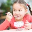 Little girl is eating ice-cream in parlor — Stock Photo #23043452