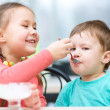 Stock Photo: Girl is feeding his little brother with ice-cream