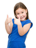 Little girl is showing thumb up gesture — Stock Photo