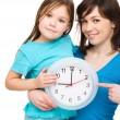 Little girl and her mother are holding a big clock - Stok fotoğraf