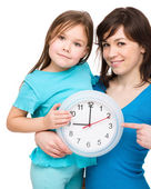 Little girl and her mother are holding a big clock — Стоковое фото